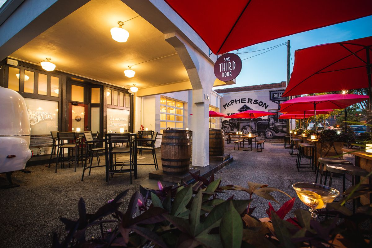 The sun setting on the patio at the Third Door bar Marietta with tables set under a porch-lit white portico in front and candlelit tables with red umbrellas beyond it