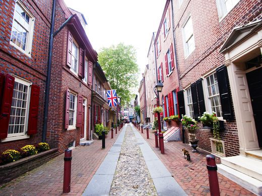 An alley in Philadelphia. The alley is narrow and there are red brick attached houses on both sides.