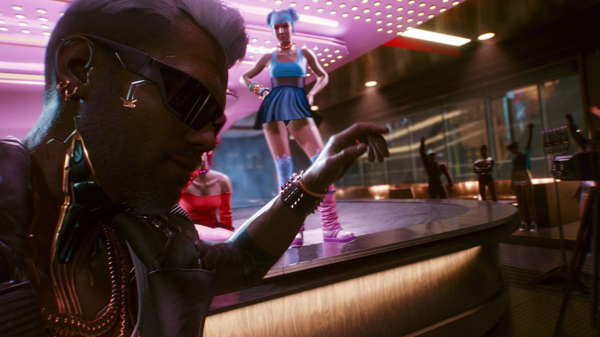 Jackie, your partner in Cyberpunk 2077, in front of a dancer at a nightclub.