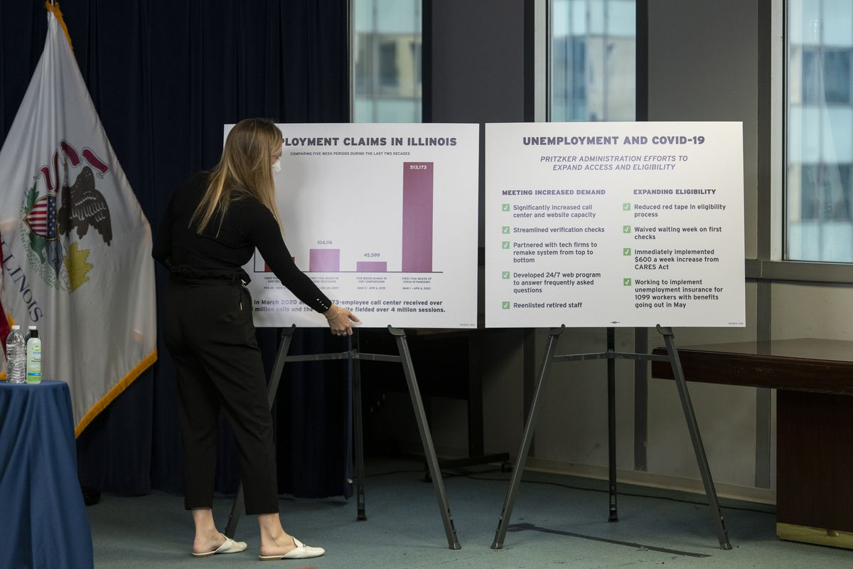 Aide to the Governor sets up information graphics on stands before Governor Pritzker's daily update to the coronavirus pandemic in Illinois, Monday, April 13, 2020.   Tyler LaRiviere/Sun-Times