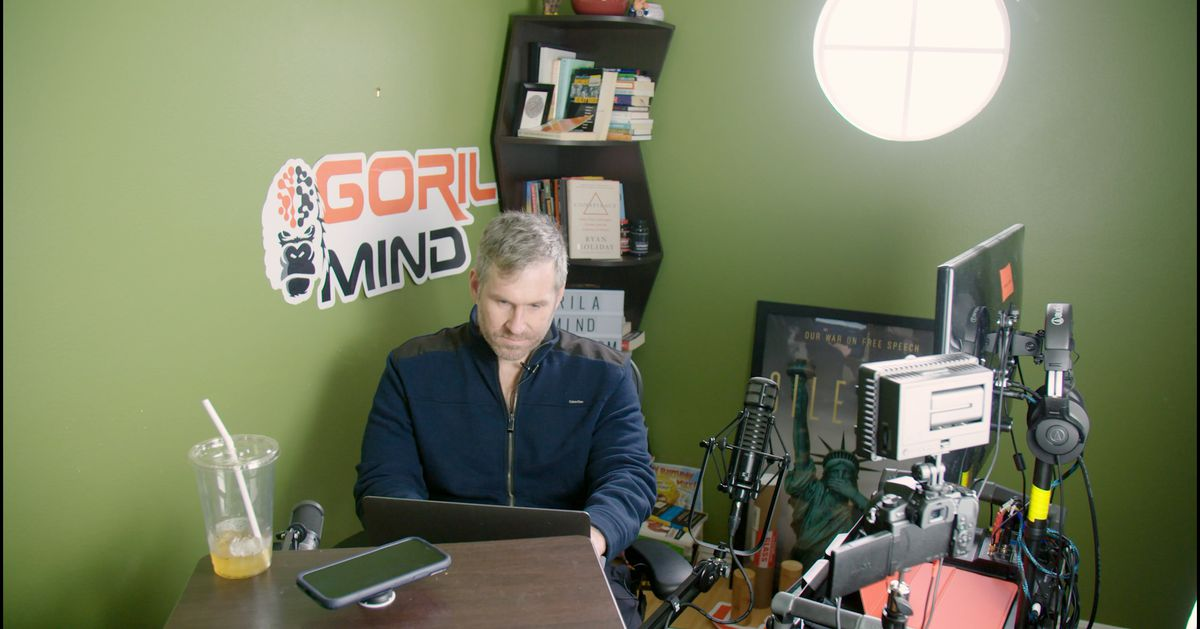 Mike Cernovich in the corner of a room in his house, with his computer and an ad for a brain supplement.
