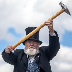 An actor portraying Union Pacific Railroad Chief Engineer and former Civil War Gen. Dodge holds up a silver maul during a reenactment of the driving of the golden spike at Golden Spike National Historic Park near Corrine, Box Elder County, on Monday, May 10, 2021. Visitors gathered at the park to mark the 152nd anniversary of the completion of the nation's first transcontinental railroad and to watch a reenactment of the 1869 ceremony.