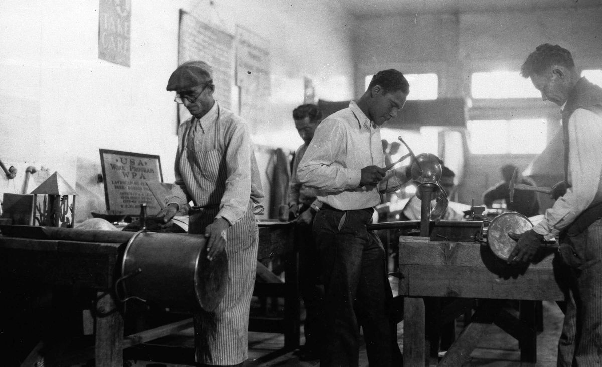 A black-and-white image from 1937 of a crew of workers fashioning medical equipment from copper.