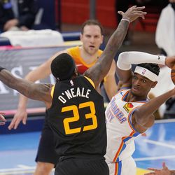 Oklahoma City Thunder guard Shai Gilgeous-Alexander, right, passes the ball around Utah Jazz forward Royce O'Neale (23) during the first half of an NBA basketball game in Oklahoma City, Monday, Dec. 28, 2020.