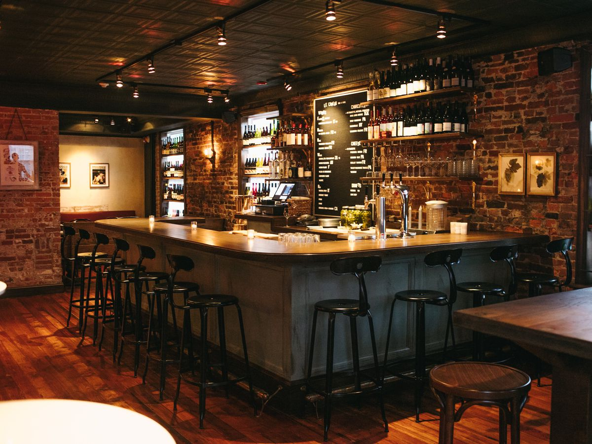 The inside of a dark wine bar with counter stools and a black and white menu and wine bottles along the back bar.