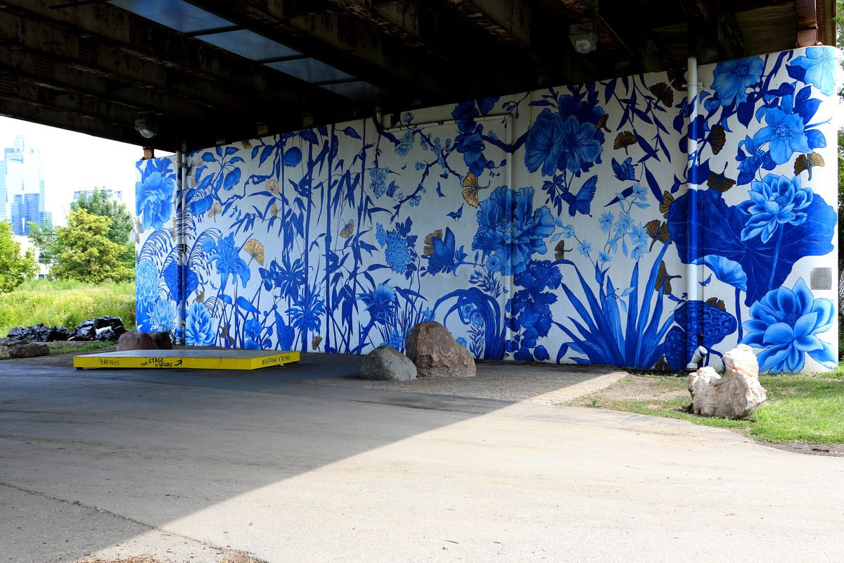 A blue and white floral mural on the wall of an underpass in a park.