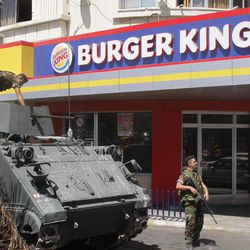 Lebanese army soldiers with their armored personnel carrier, stand guard outside a Burger King as part of stepped up security measures in the southern port city of Sidon, Lebanon, Saturday Sept. 15, 2012. Angry protesters attacked on Friday a Hardees and Kentucky Fried Chicken outlets in Tripoli north Lebanon to protest against a movie that insults Prophet Muhammad.