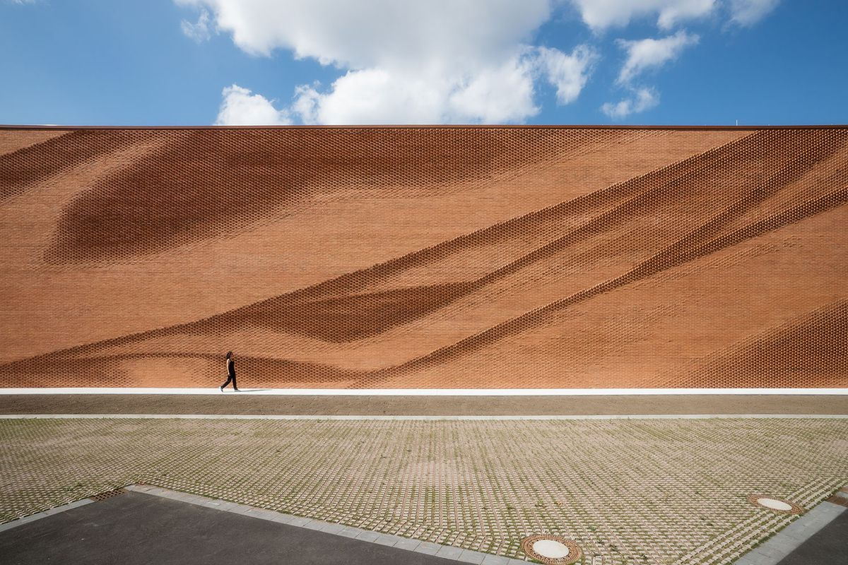Woman walking in front of red brick wall