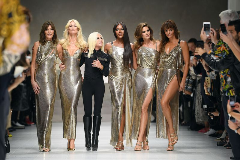 Versace, dressed in black, and the supermodels, dressed in liquid gold gowns, walk arm in arm.
