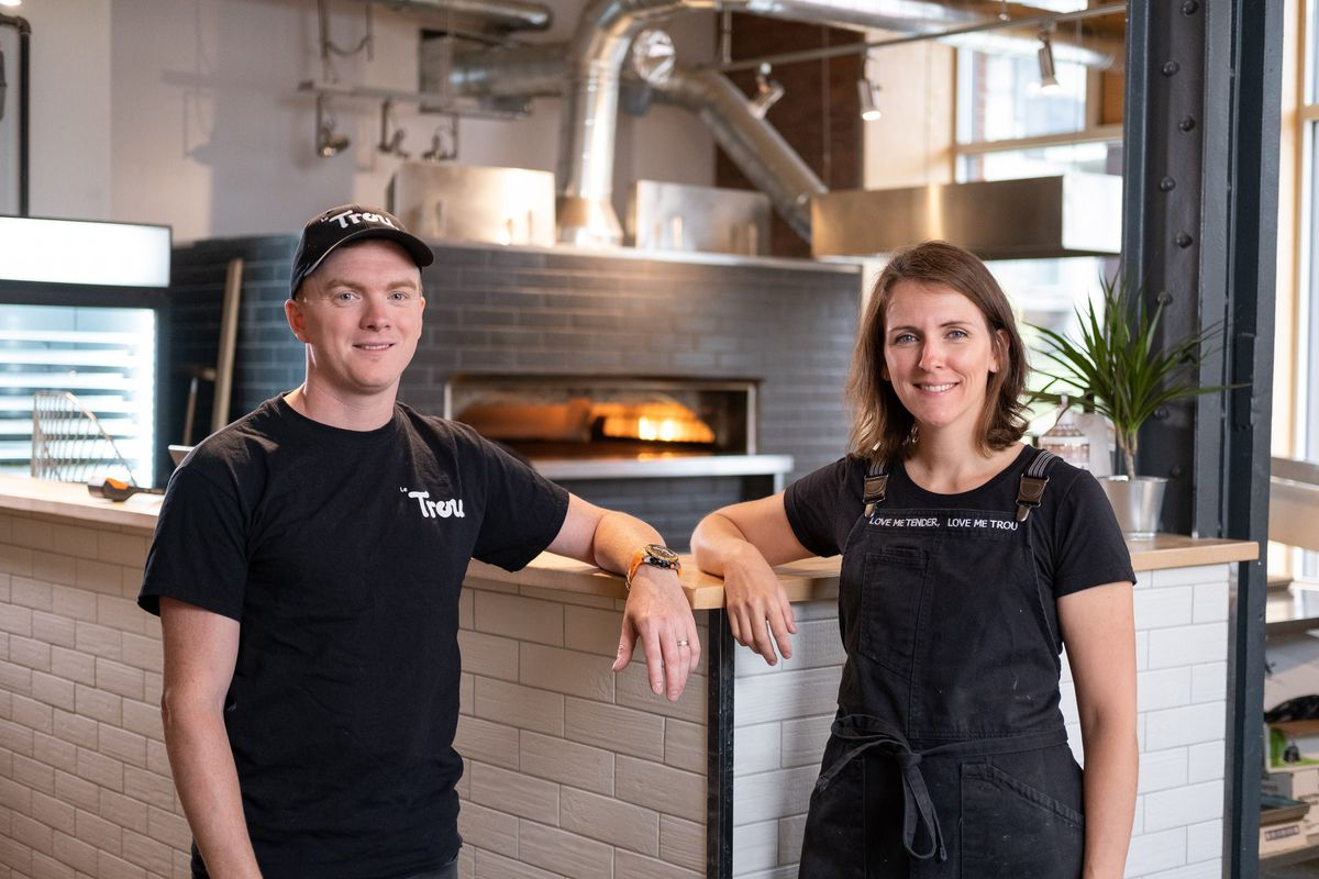 Damien Cussac and Alexandra Grenier stand in front of their bagel oven at Le Trou.
