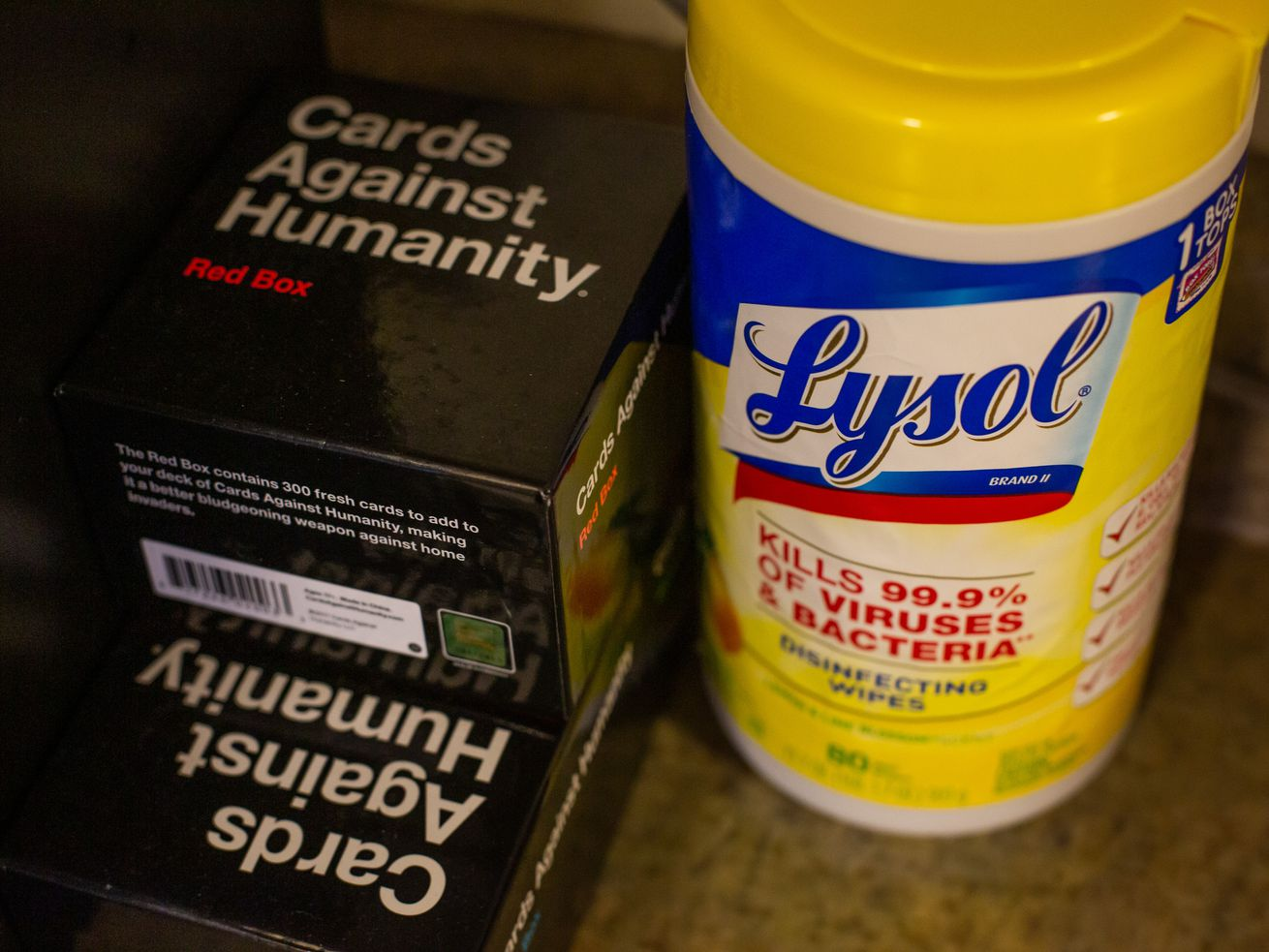 Lysol wipes and a Cards Against Humanity game sit on a counter together.