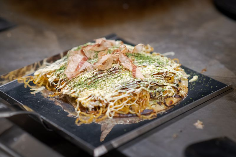 A savory Japanese pancake on a plate with a variety of toppings.