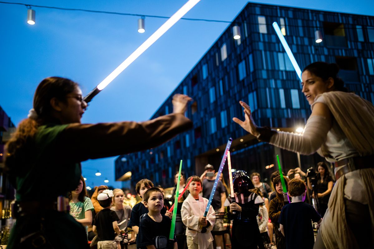 A woman dressed up as Princess Leia and a guy fighting with light sabers in from of a crowd