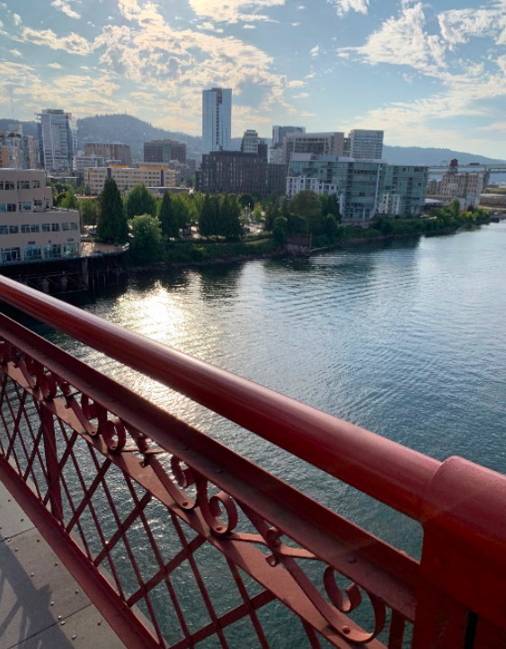 The rust-colored decorative steel of a bridge is seen in the foreground with a wide river and buildings of downtown Portland in the distance.