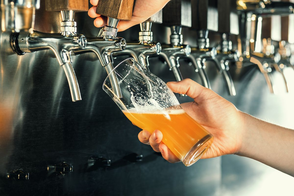 Hands pour beer from a tap into a pint glass.
