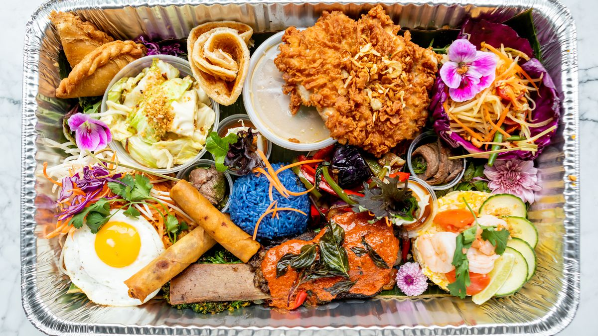 A metal tray is filled with rolls of roti, rice, fried chicken, panang curry-covered short ribs, and more from Farmhouse Kitchen