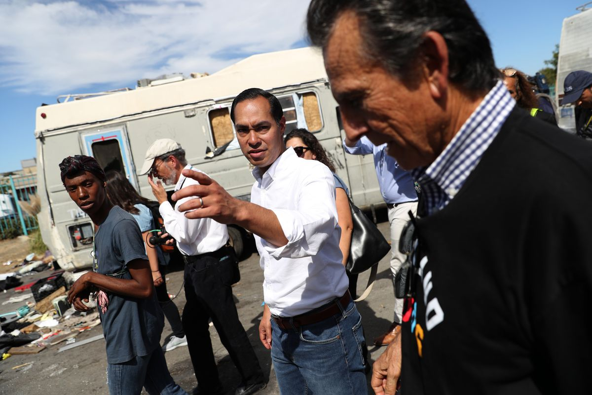 A group of men, including a Hispanic man at the center wearing a white dress shirt with the sleeves rolled up, walk past a blue trailer and ground strewn with trash.