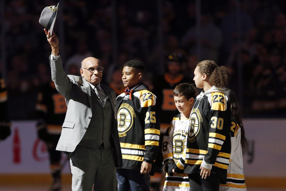 Hockey Hall of Famer Willie O'Ree, right, waves to the crowd before dropping the ceremonial puck before a Bruins game last January. The Bruins announce they will retire O'Ree's No. 22 jersey.