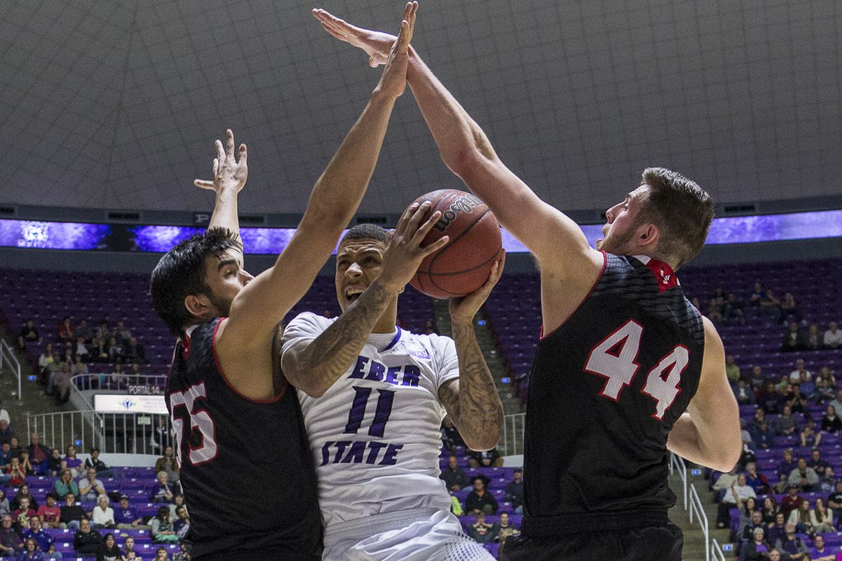 Venky Jois (55) and Felix Von Hofe (44) smother Weber State's Chris Golden (11) during Eastern Washington's victory Saturday night, clinching a conference co-championship for the Eagles.