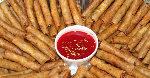 A tray full of lumpias and bright red dipping sauce from Fredcel.