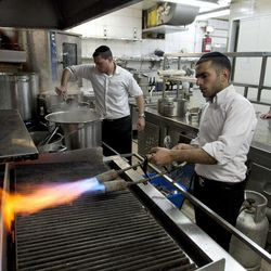 In this Thursday April 5, 2012 photo, chef Noam Dekkers , in the back, watches workers of the Tel Aviv-Jaffa rabbinate blow-torch the grill stove in one of the kitchens in Liliyot restaurant making it kosher for the Jewish holiday of Passover, in Tel Aviv, Israel. The Jewish springtime holiday Passover is known as a festival of freedom, but its hallmark is a litany of dietary restrictions centered on not eating leavened bread for a week. The rules are so elaborate that chefs who want to observe the ritual law must prepare weeks before, cleaning away every last crumb, buying up doubles of kitchen utensils, and planning menus without bread or regular flour. Standing back right is chef Noam Dekkers.