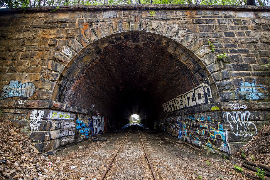 A long tunnel of stone and brick with railroad tracks shown beneath.