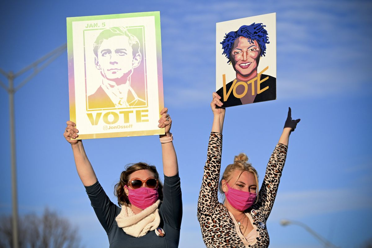 """Two women in pink breathing masks hold up """"vote signs, one with a drawing of Jon Ossoff and one with a drawing of Stacey Abrams."""