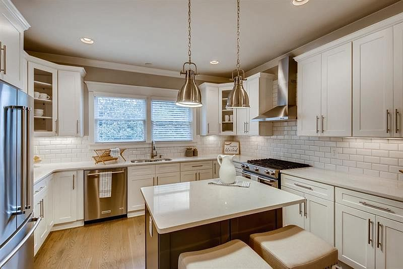 A white kitchen with a stainless steel fridge at left.