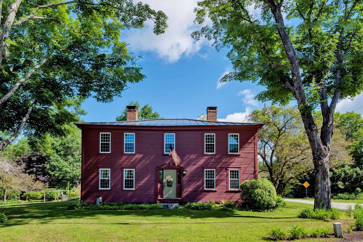 A two-story wood-frame colonial with dark red exterior and two chimneys set on grassy site.