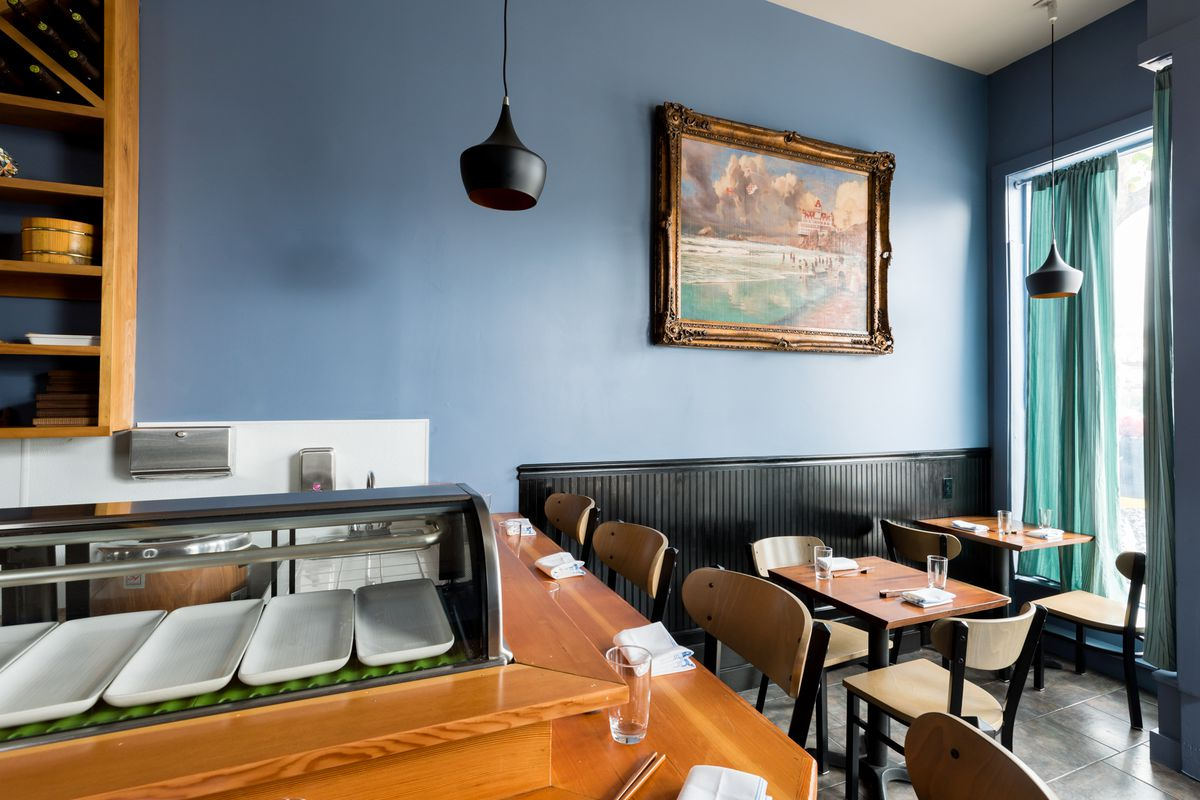 The corner of the sushi bar with a large painting in the background.