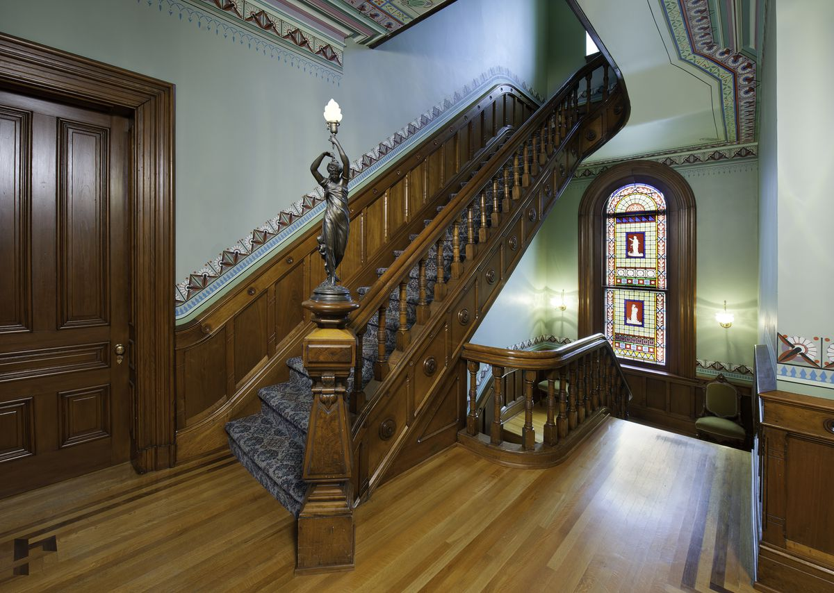 A formal foyer has wood floors, an elaborate wood staircase with intricate carving, teal walls, and a stained glass window in the hallway.