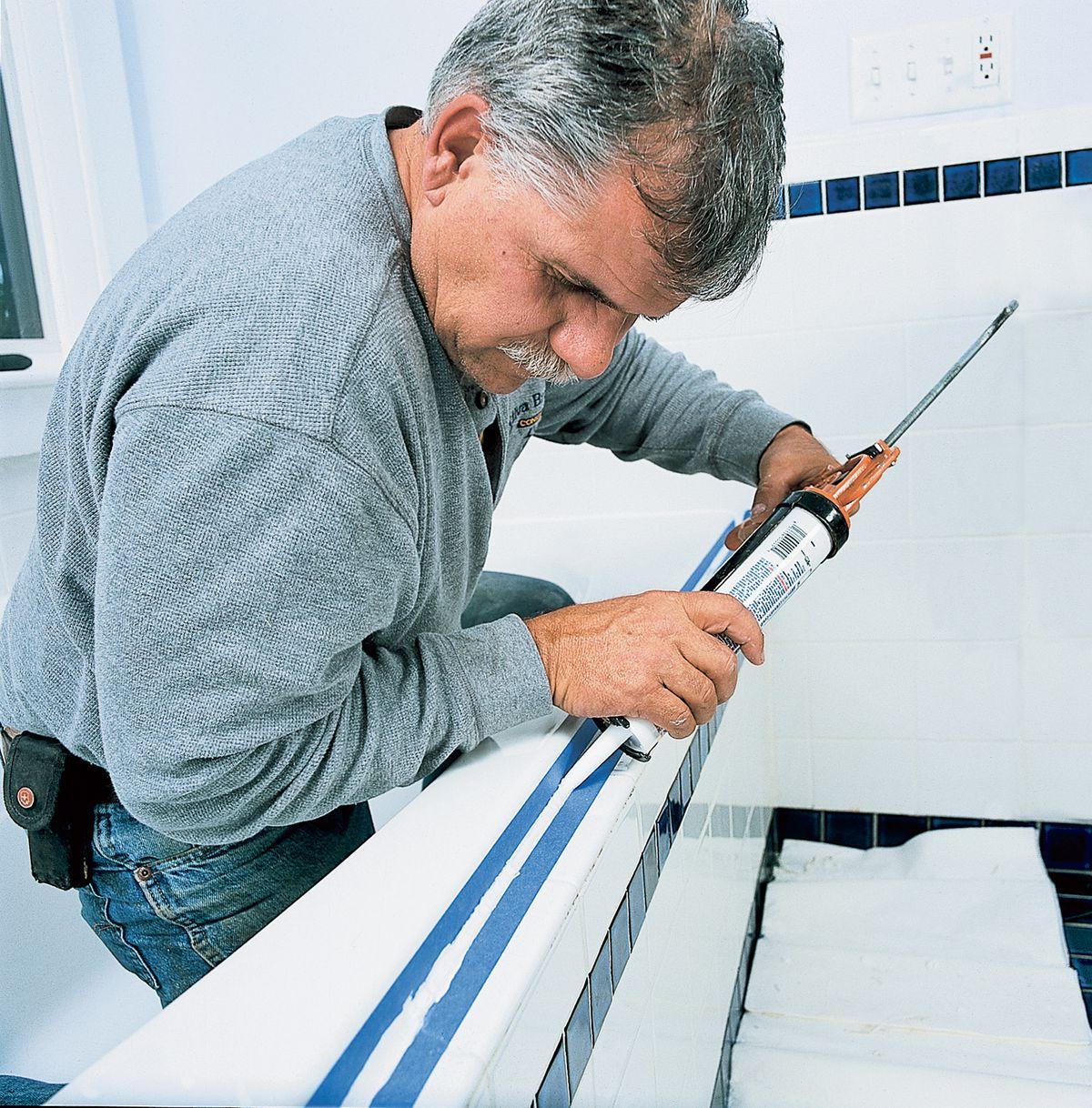 Man Caulking Bathroom