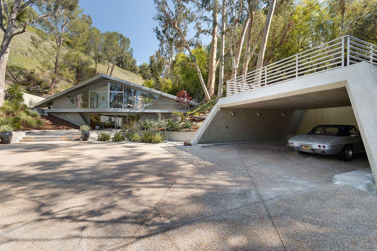 A photo of a house and angular concrete carport.