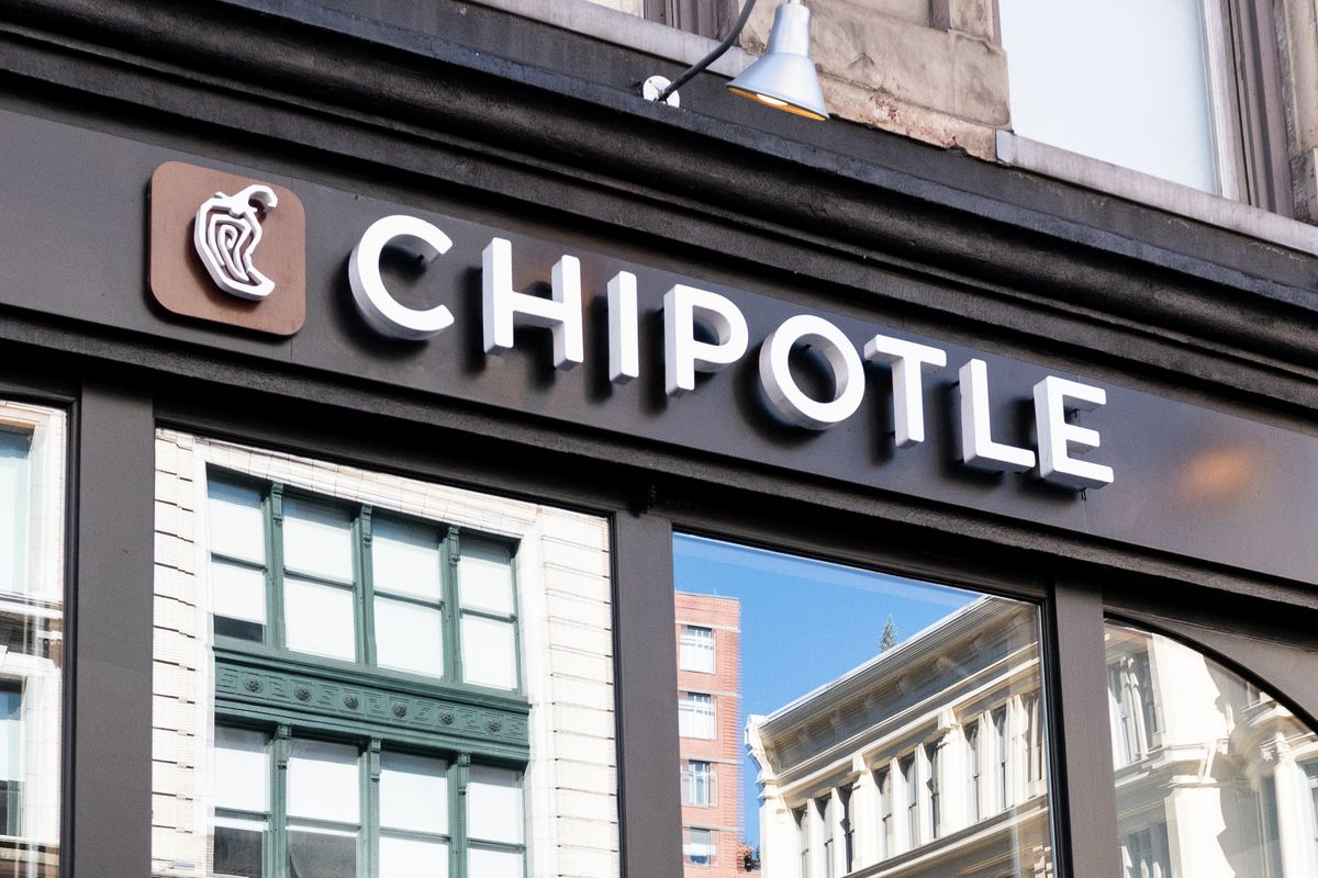 A Chipotle sign with the reflection of a New York City skyline. Next to the sign, the company's chili pepper logo gleams.
