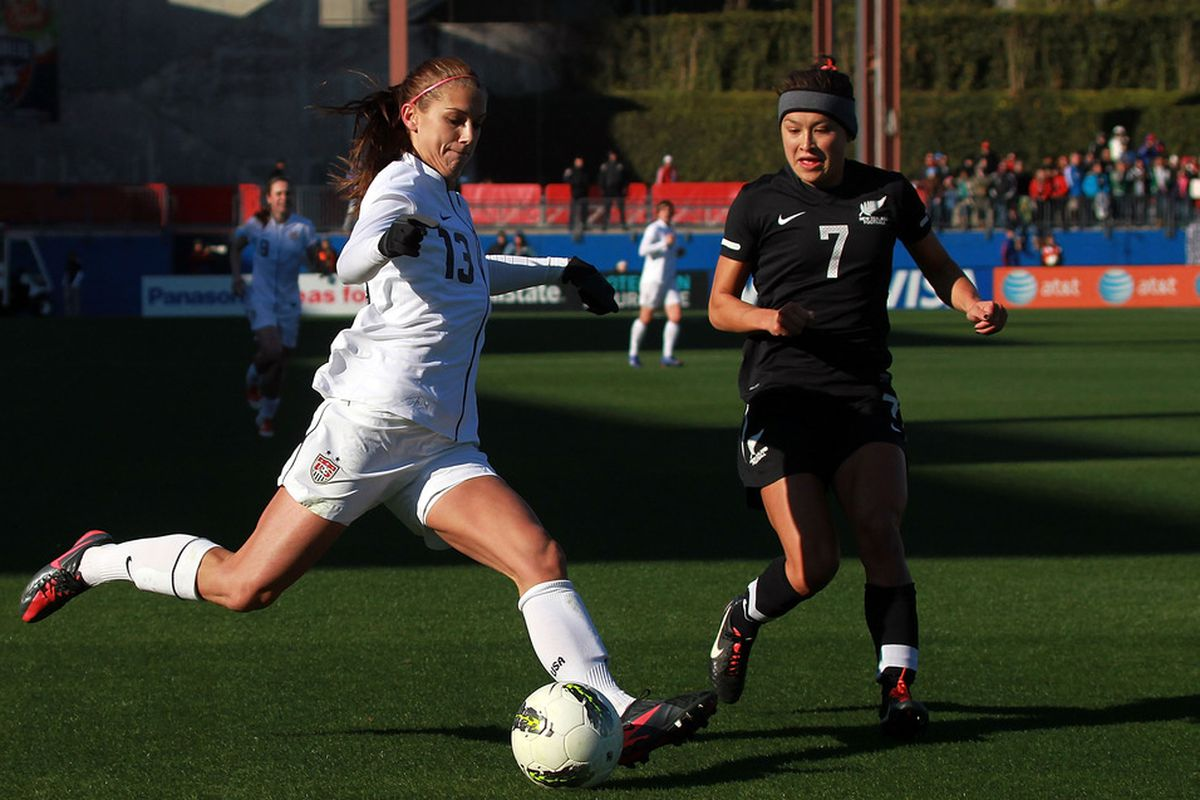 FRISCO, TX - FEBRUARY 11:  Alex Morgan #13 of USA dribbles the ball past Ali Riley #7 of New Zealand during an international friendly at FC Dallas Stadium on February 11, 2012 in Frisco, Texas.  (Photo by Ronald Martinez/Getty Images)