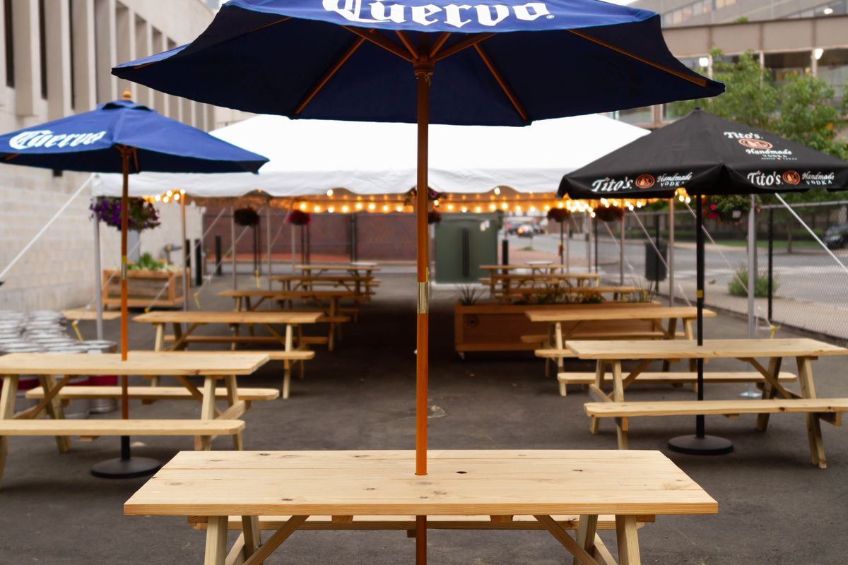 A parking lot beer garden, with picnic tables under umbrellas