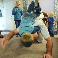 8-year-old Mykenzie Burton watches as dad, Kelly, flips 6-year-old Porter off his back while 3-year-old Logan, right, plays with mom at the family's home Sept. 25.
