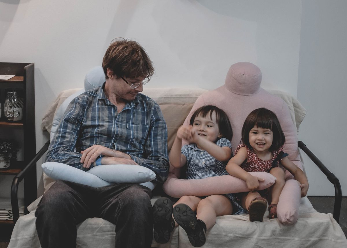 Two kids and an adult sitting with headless pillows