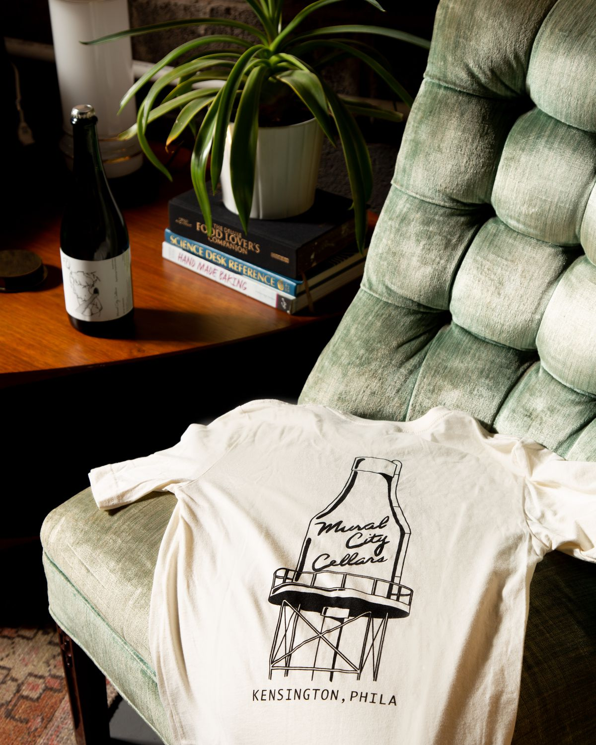 a mural city cellars t-shirt draped over a velvet green couch