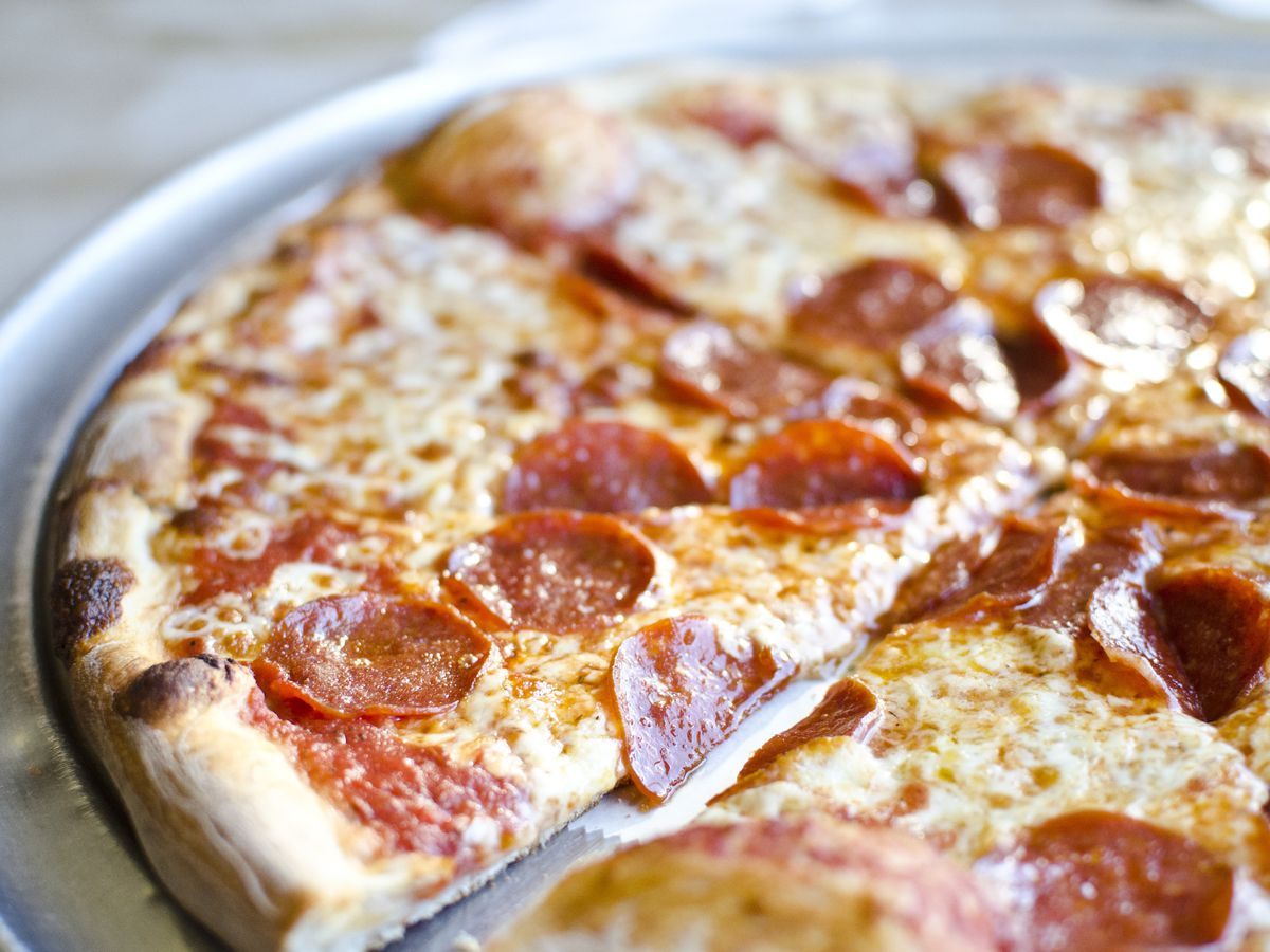 Partial view of a pepperoni pizza on a metal tray on a light-colored table