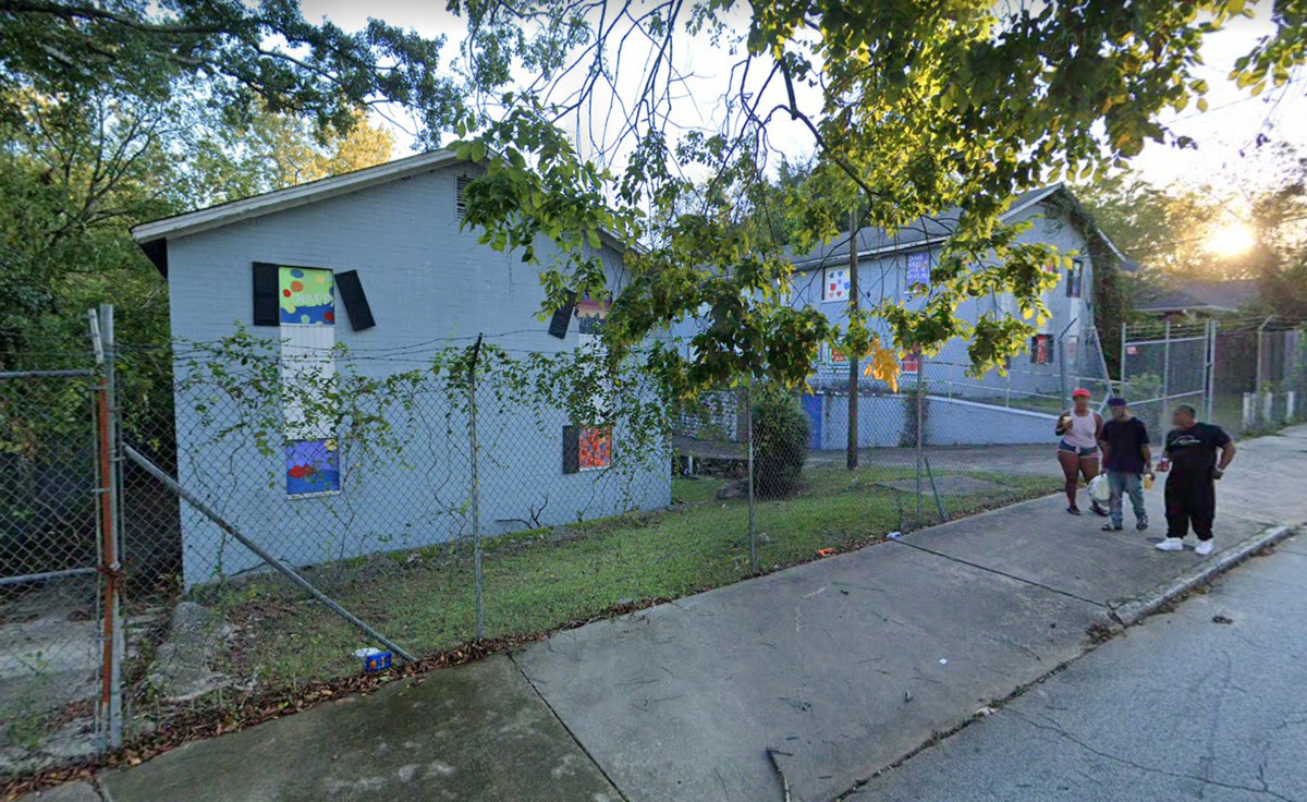 Three people walk down a sidewalk in front of a fenced-off, boarded-up apartment project.