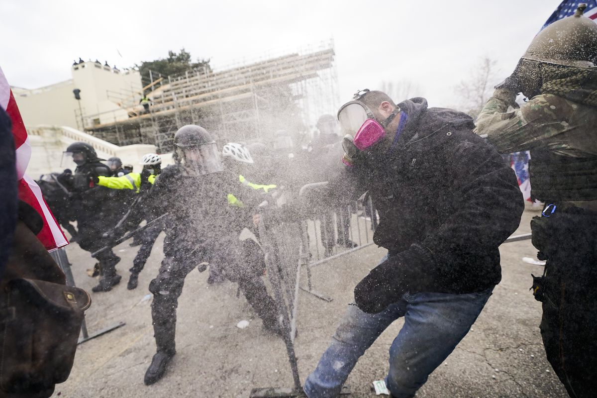 A man in a gas mask jumps back, recoiling from a cloud of what appears to be pepper spray. A police officer in black riot armor takes an aggressive stance in front of the man, his baton extended and ready to strike.