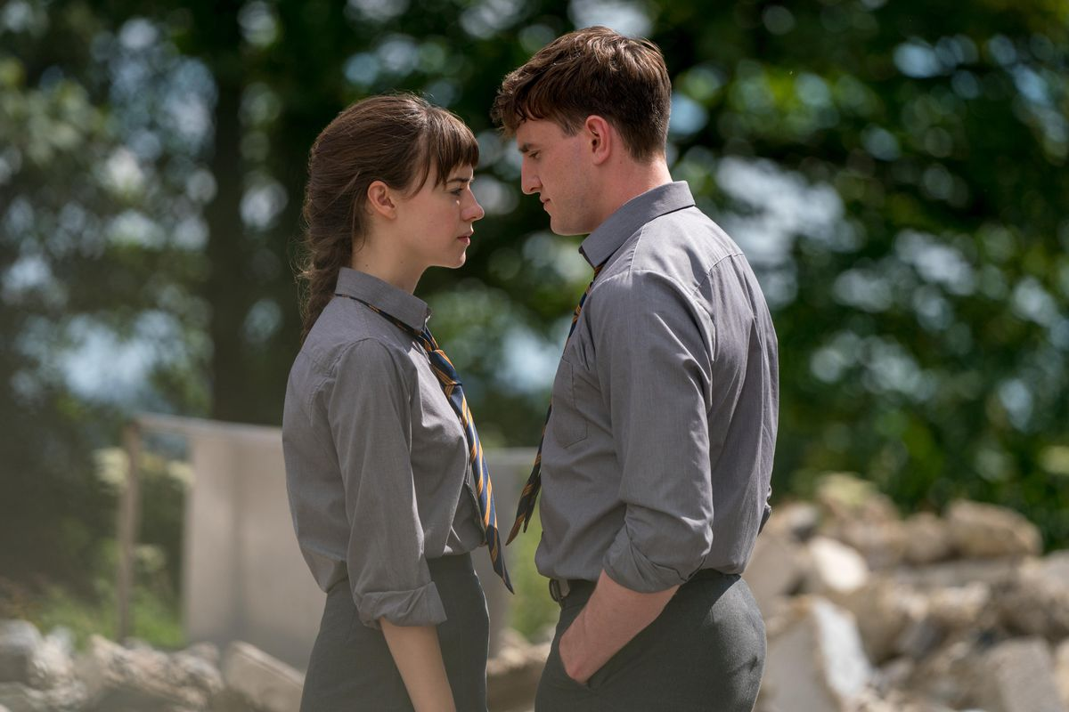 A young man and woman stand outdoors, wearing matching school uniforms, facing each other and standing very close