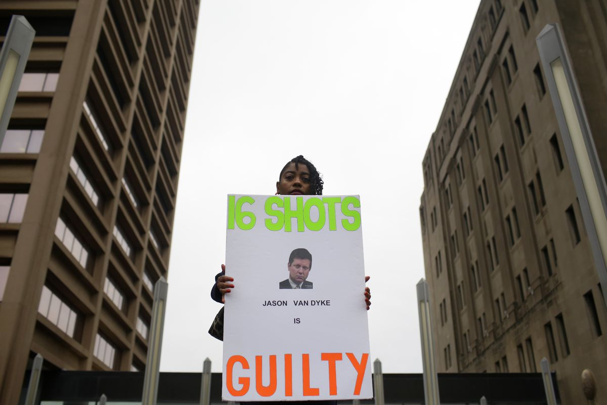 A woman holds a sign outside the courthouse after a murder verdict is handed down in the trial of Chicago Police Officer Jason Van Dyke.