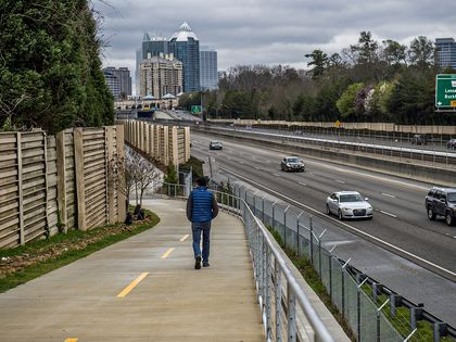 A highway with a walking path next to it. There is a man walking down the walking path. There are cars on the highway. In the distance is a city skyline.