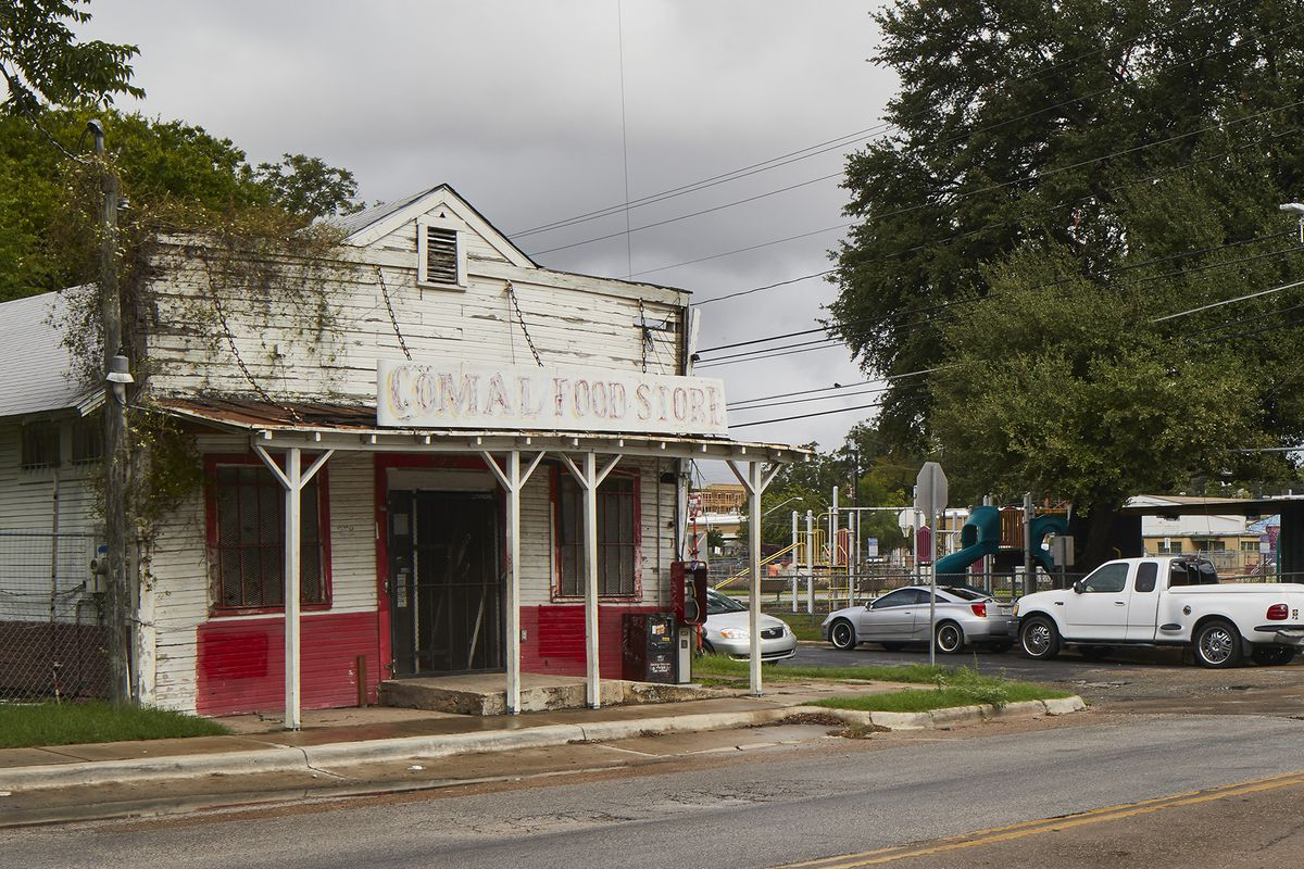 Old one-story wooden building painted white with red skirting and trim.
