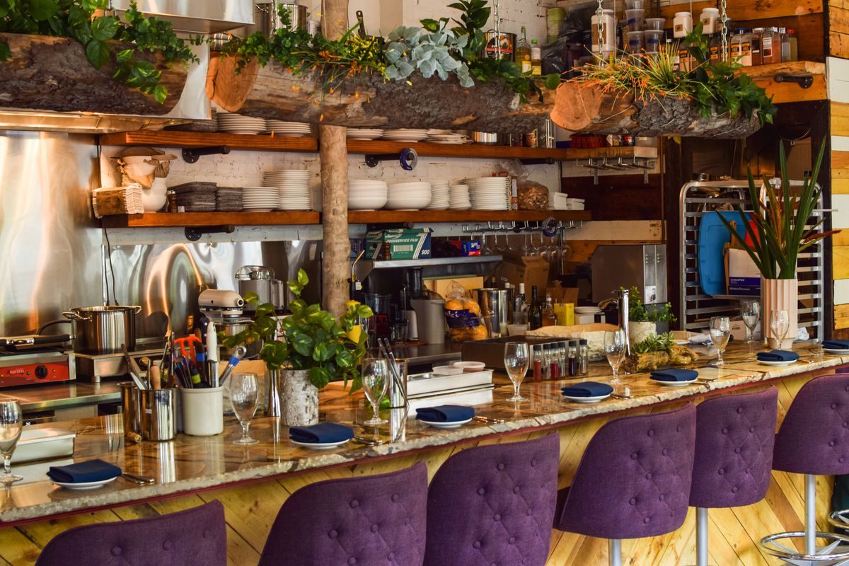 Purple bar chairs lined up at Avant Garden's bar with plates and glasses set out