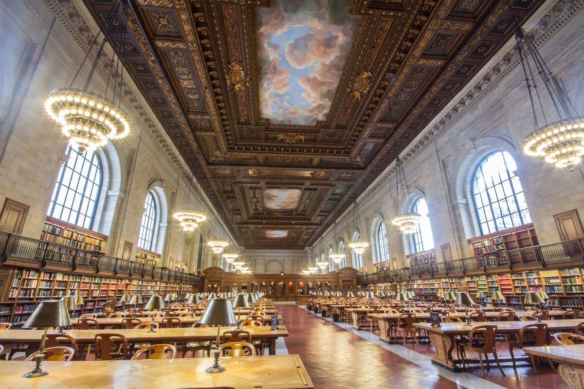 The interior of the reading room in the New York Public Library. The ceiling has ornate carvings and a mural of a sky with clouds. There are multiple hanging chandeliers. On the floor are rows of tables and chairs.