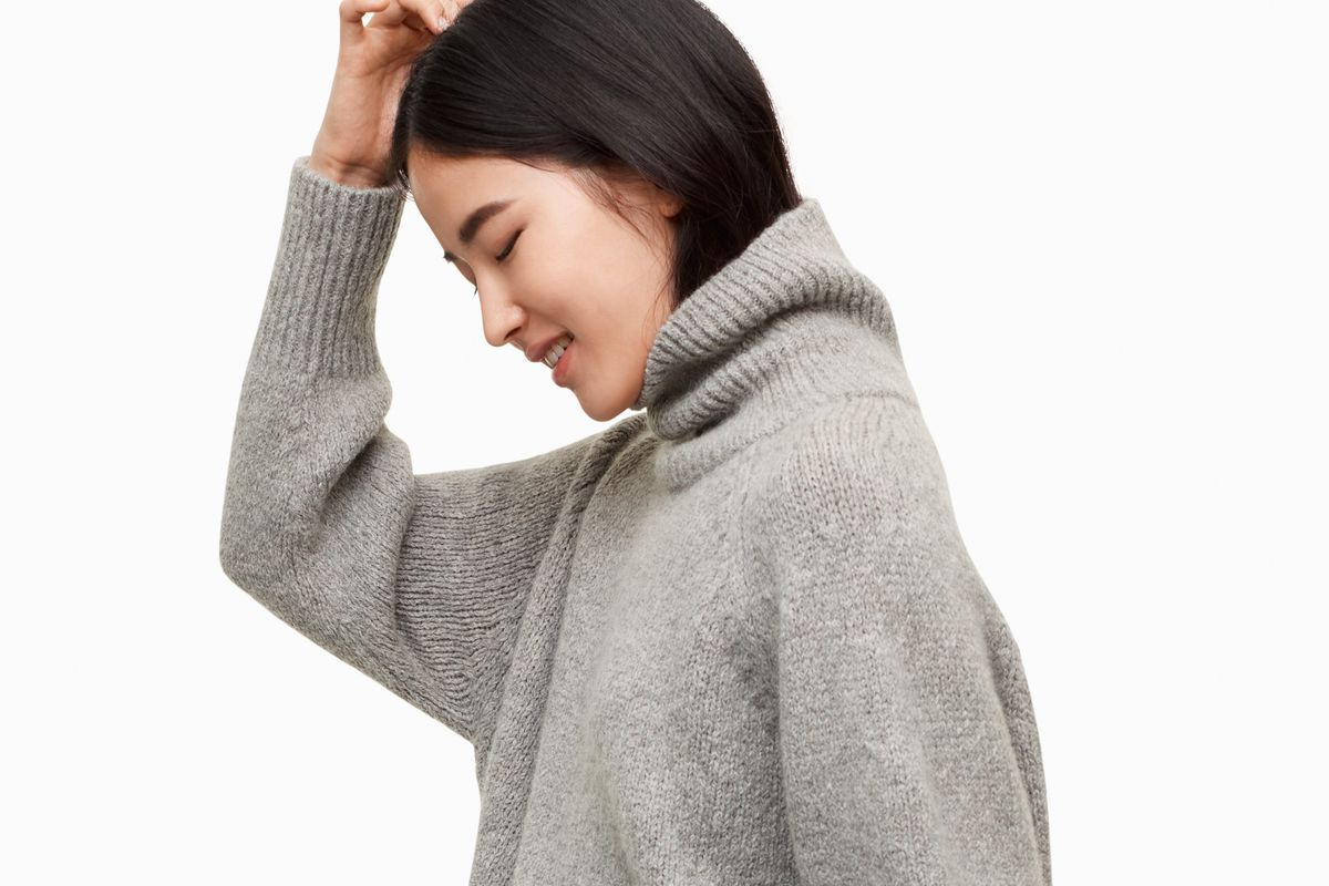 A woman in a gray turtleneck sweater
