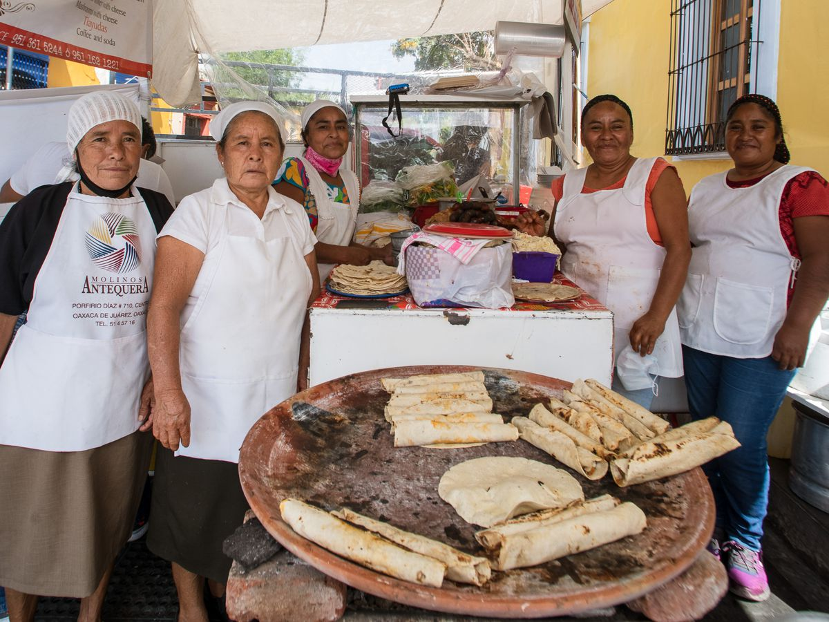 A group of women in aprons stand around a comal with many tacos.